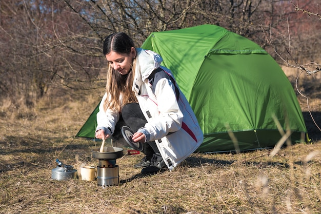 Cheerful woman camping alone cooking in front of her tent