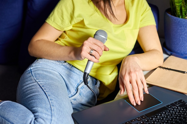 Cheerful woman in casual clothes recording a podcast, talking into a microphone with headphones and laptop, notebook