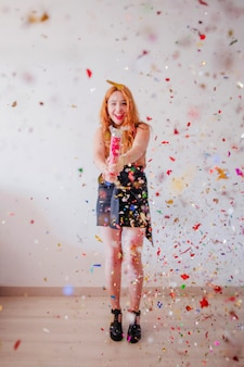 Cheerful woman celebrating with party popper