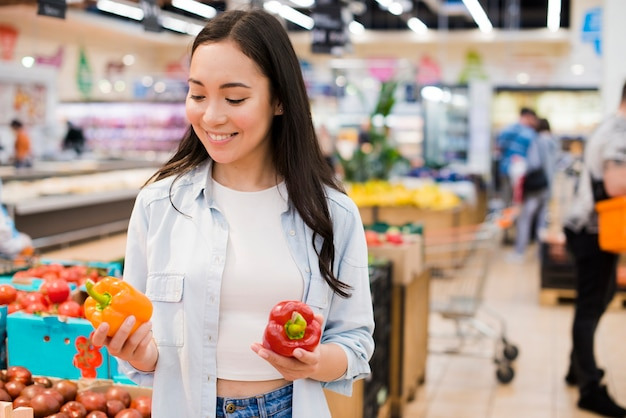 Cheerful woman choosing bell pepper in grocery store