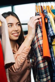 Веселая женщина, выбирающая одежду в магазине