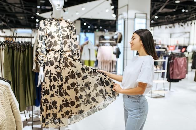 衣料品店でドレスを選ぶ陽気な女性