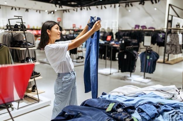 衣料品店でジーンズを選ぶ陽気な女性
