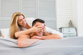Cheerful woman closing eyes to young smiling man in bed