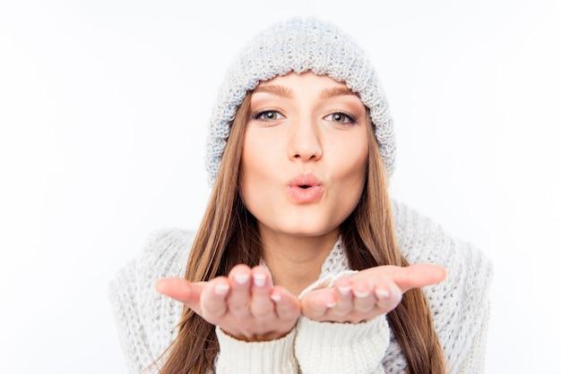 暖かい帽子とスカーフで陽気な女性の服は空気のキスを送信します