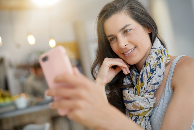 Cheerful woman in coffee shop using smartphone for video call
