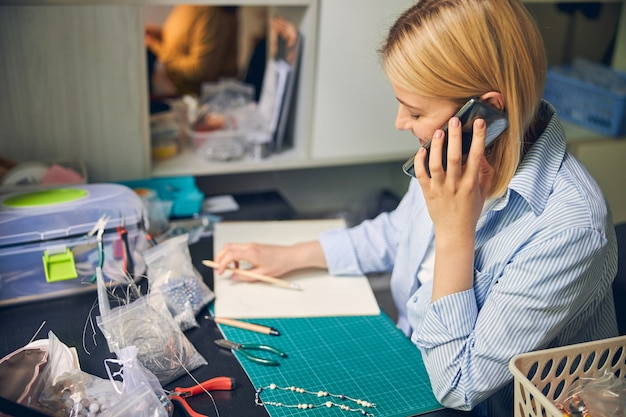 Веселая женщина общается через смартфон во время рисования эскиза ожерелья