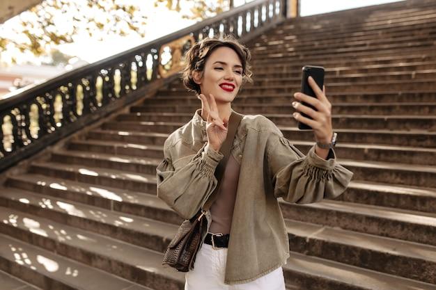 Donna allegra in giacca fresca e jeans leggeri che fanno selfie. la giovane donna con capelli ondulati mostra il segno di pace all'esterno.