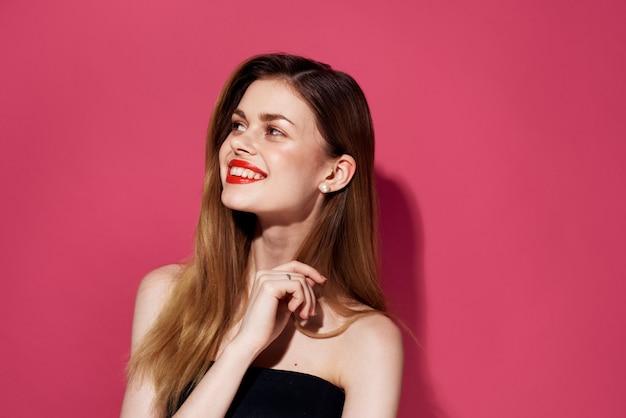 陽気な女性の化粧品赤い唇の笑顔が魅力的なピンクの背景に見えます。