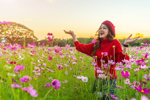Cheerful woman in cosmos flower field with sunset