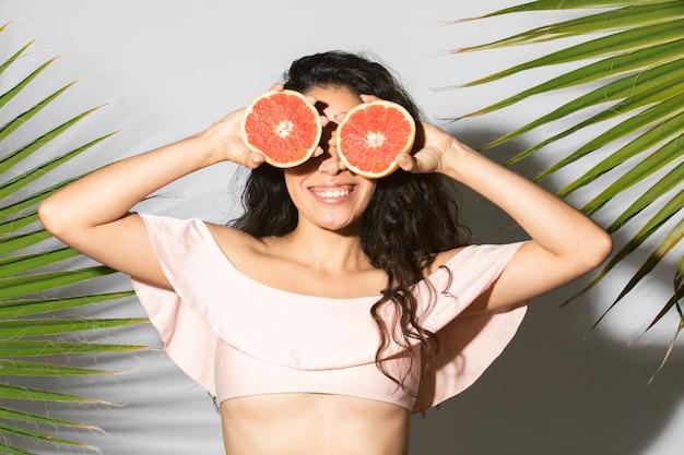 Веселая женщина закрыла глаза нарезанным грейпфрутом