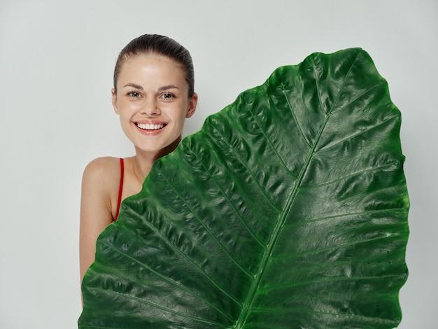 陽気な女性は緑の葉の笑顔の明るい背景で体をカバーします