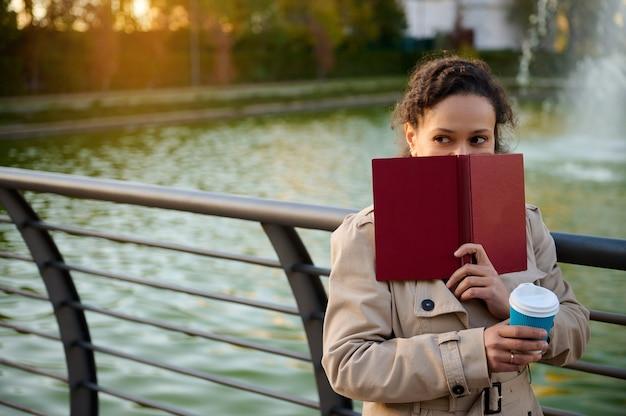 쾌활한 여성은 양장본 책으로 얼굴을 가리고 옆을 바라보고 호수를 배경으로 서서 뜨거운 커피가 담긴 컵을 들고 있습니다. 가을 배경, 야외 활동, 가제트에서 휴식