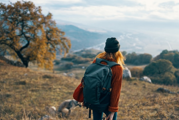 Cheerful woman creates a backpack on a trip walk landscape