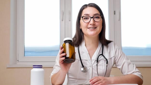 안경과 청진기를 갖춘 쾌활한 여성 의사 블로거는 병원 사무실 창가 근처 테이블에 앉아 카메라에 약이 든 병을 보여줍니다.