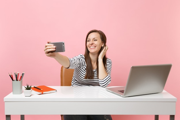 Cheerful woman doing taking selfie shot on mobile phone while sit working at white desk with contemporary pc laptop