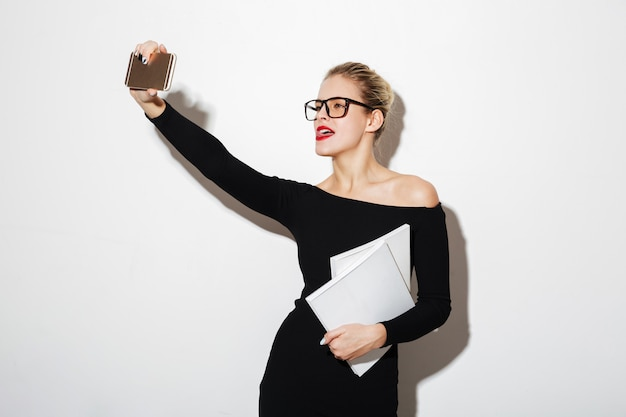 Cheerful woman in dress and eyeglasses making selfie on smartphone