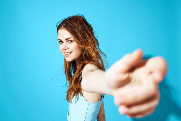 手で身振りで示す陽気な女性のドレスグラマークロップドビューブルー分離。