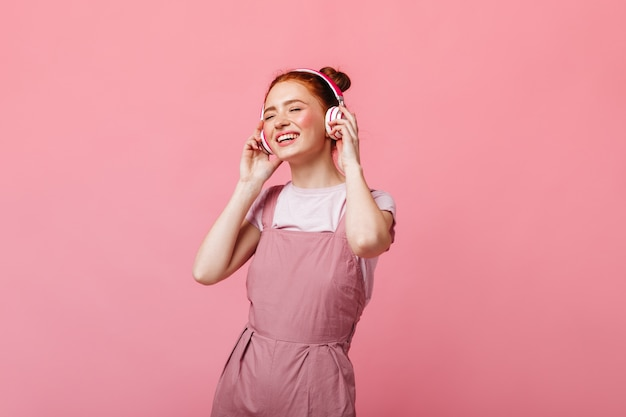 Cheerful woman dressed in light overalls dancing and listening to music on headphones on pink background.