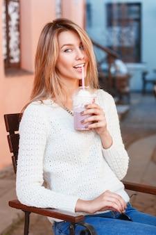Веселая женщина пьет коктейль в жаркий летний день