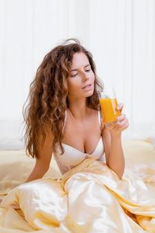 Веселая женщина пьет апельсиновый сок, сидя на кровати у себя дома