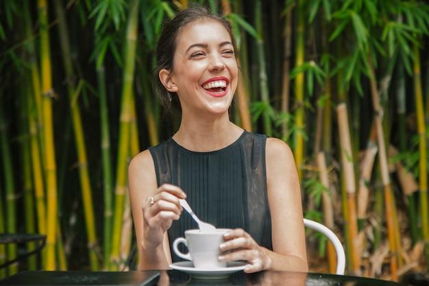 Жизнерадостная женщина пьет кофе во франции