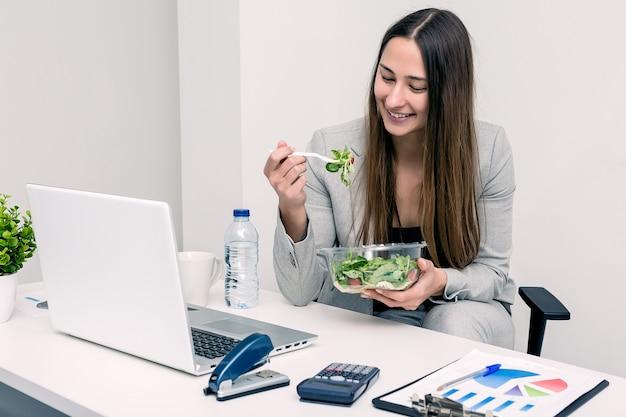 オフィスでサラダを食べる陽気な女性