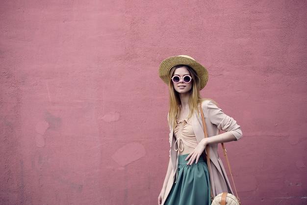 陽気な女性エレガントなスタイルの壁の背景上の旅行ライフスタイル。