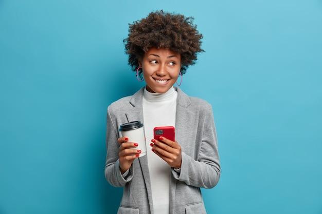 Imprenditrice donna allegra posa con caffè da asporto e smartphone, lavora su un nuovo progetto di business, digita alcune note, vestito con abiti formali, pose