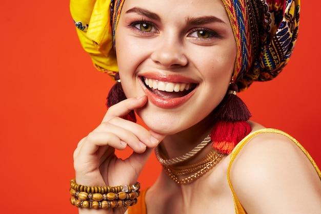 陽気な女性の民族性色とりどりのヘッドスカーフメイクグラマー赤い背景。高品質の写真