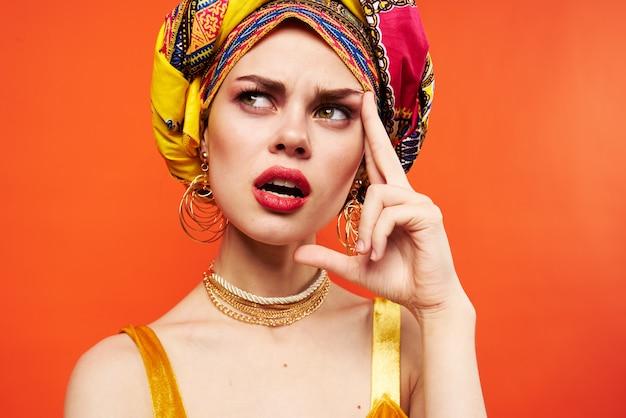 陽気な女性の民族性色とりどりのヘッドスカーフメイクグラマー赤い背景