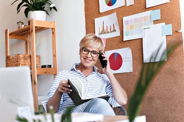 La donna allegra in occhiali pone in ufficio e parla al telefono