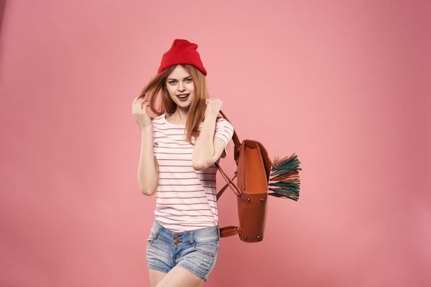 쾌활 한 여자 패션 옷 배낭 스튜디오 핑크 벽.