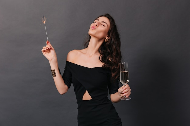 Cheerful woman in fashionable dress posing with glass of champagne and sparkler. lady sends kiss on black background.