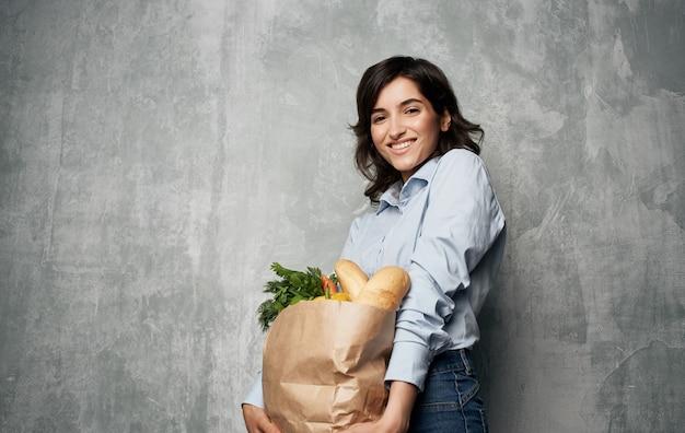 Жизнерадостная женщина от доставки супермаркета торговый пакет здоровой пищи.
