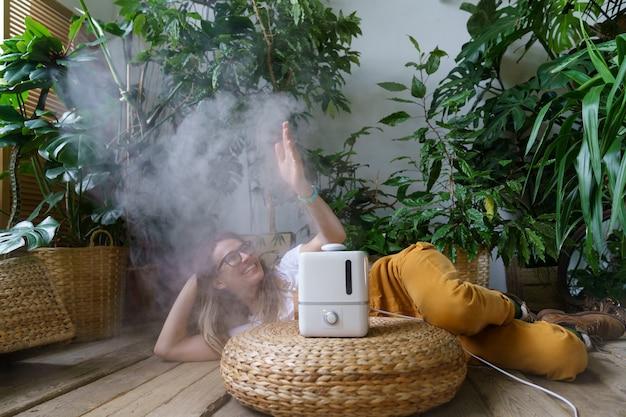 쾌활한 여성 정원사는 상록 식물이 있는 가정 정원의 가습기에서 신선한 공기 증기를 즐깁니다.