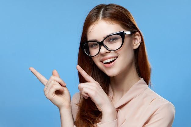 Жизнерадостная женщина, показывающая пальцем в очках, эмоции обрезанная синяя стена.