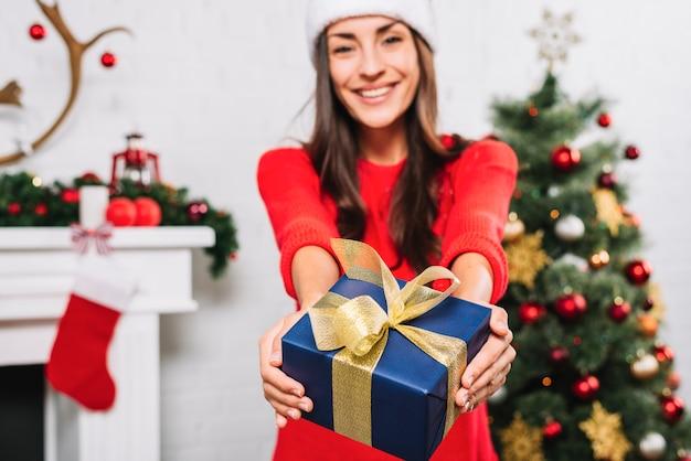Cheerful woman giving present box