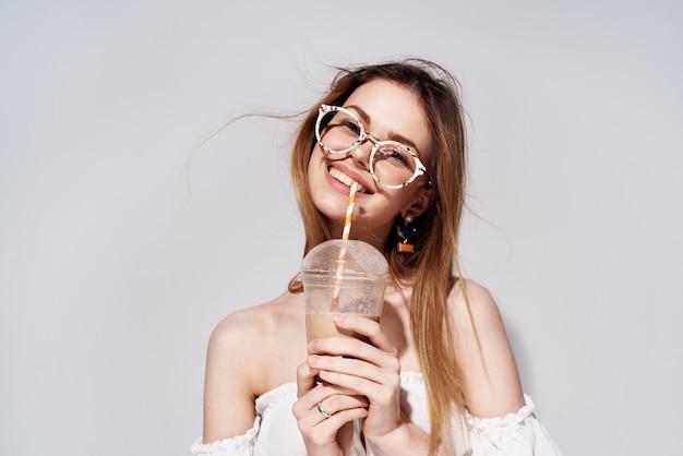 Жизнерадостная женщина стакан с напитком очарование улыбка светлом фоне.