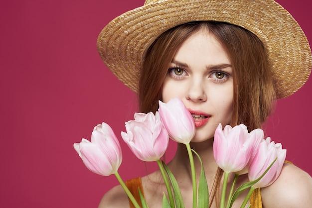陽気な女性の黄金のドレスの花束の花の休日ピンクの背景