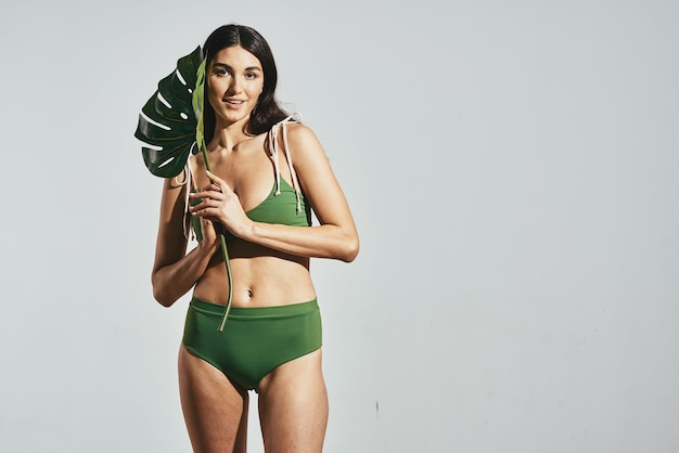 Cheerful woman in green swimsuit palm leaf beach gray background