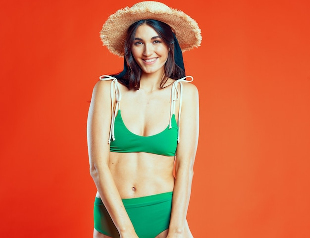 Cheerful woman green swimwear beach hat red background glamor