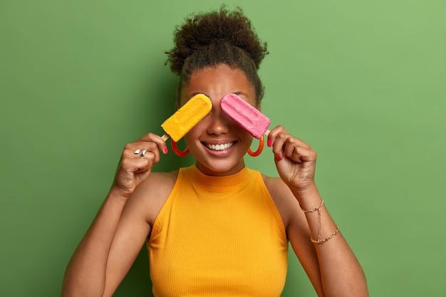 쾌활한 여자는 재미 있고 이빨 미소 짓고 아이스크림으로 눈을 가리고 노란색 옷을 입은 진정한 긍정적 인 감정을 표현하고 실내에서 포즈를 취합니다. 사람, 여름, 디저트 및 먹는 개념.