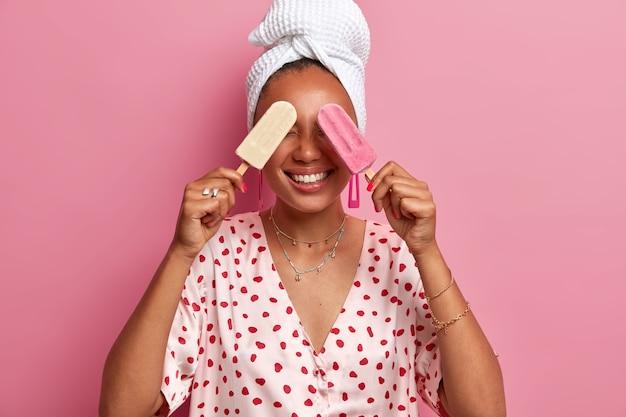 陽気な女性は夏の暑い時期にアイスクリームを楽しんで、凍ったアイスキャンディーで目を覆い、気分が良く、国産のガウンと包まれたタオルを頭に着ています。女性はおいしいサンデーを持っています。