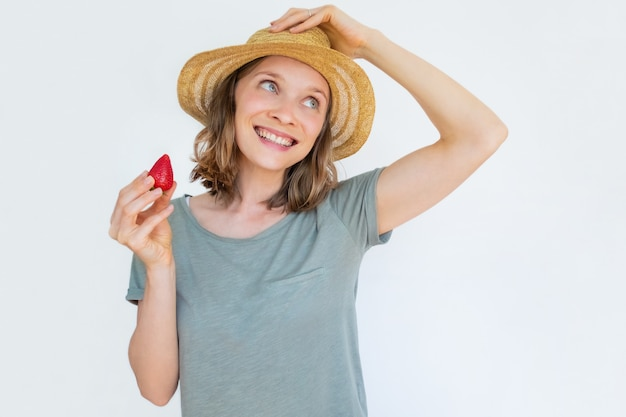 Cheerful woman in hat holding ripe strawberry and smiling