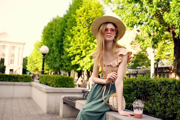 Cheerful woman in a hat in the park drink rest fresh air. high quality photo