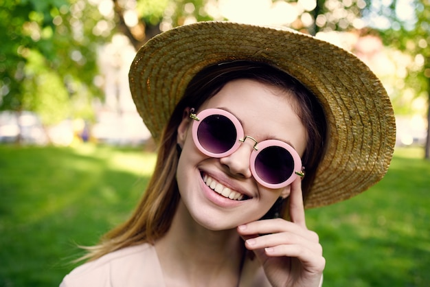 Cheerful woman in hat wearing sunglasses outdoors in the park grass walk. high quality photo