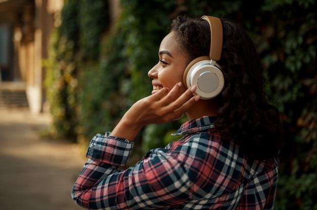 Cheerful woman in headphones listening to music in summer park. female music fan walking outdoors, girl in earphones, green bushes