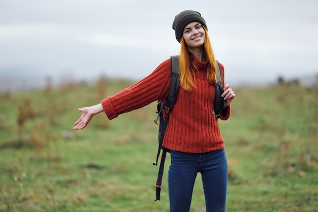Cheerful woman hiker in autumn clothes with a cutter in the mountains landscape on a trip