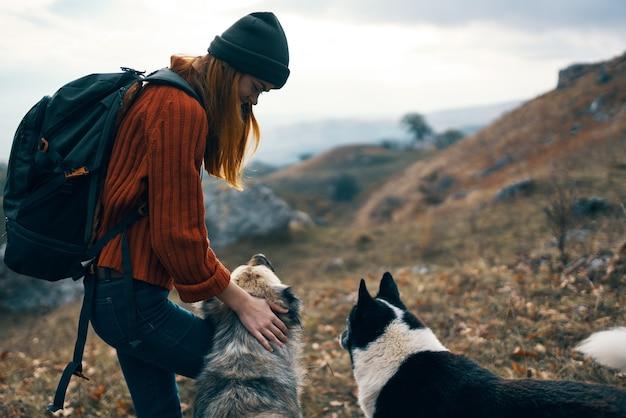 Веселая женщина турист на открытом воздухе горы собаки путешествия дружба